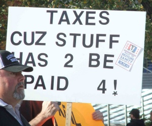protestor holding sign--Taxes Cuz Stuff Has 2 Be Paid 4