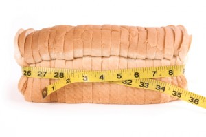 loaf of white bread with measuring tape around its waist