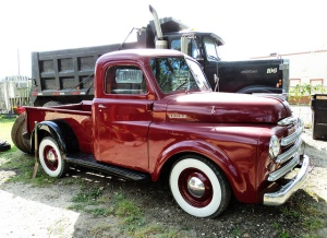 1949 Dodge Pickup Dark Cherry next to tandem dump truck